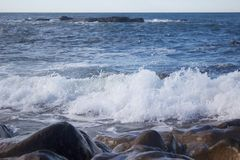 Rocks near the Portugese sea, water rising. Rocks near the portugese sea, water is rising and smashing to the rocks royalty free stock photos