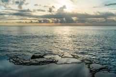 Rocks near the sea. Sunset sky reflected in the pools Stock Images