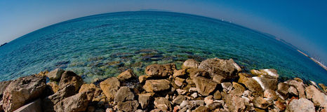 Rocks near a sea. A wide angle picture of Rocks near a sea in a beach resort in Athens Greece,in a summer day of april Stock Image