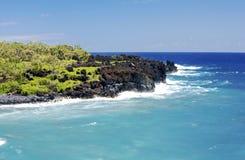 Rocks in the Ocean. Black rocks on the shore of Hana in Hawaii stock photos