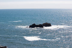 Rocks in the ocean. Rocks in the calm blue ocean and horizon Royalty Free Stock Image