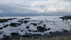 Rocks in the ocean and clouded sky Stock Photo