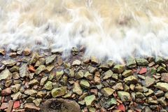 Rocks and Ocean Froth. The rocks of an ocean beach are continuously washed by the frothy waves Stock Images
