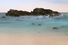 Rocks in the ocean on the horizon after sunset Stock Image