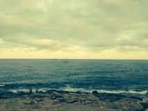 Rocks and ocean scene in Spain with sailboat in di Royalty Free Stock Images