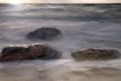 Rocks at ocean shore. Ocean waves hitting rocks on the shore at sunset Stock Image