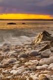 Rocks at Osmington Reflecting Sunset Colours Royalty Free Stock Photo