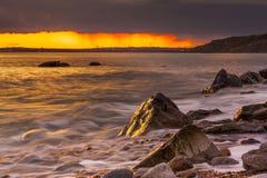 Rocks at Osmington Reflecting Sunset Colours Royalty Free Stock Images