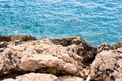 Rocks over azure sea Stock Photos