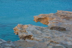 Rocks overhanging the blue sea Stock Photo