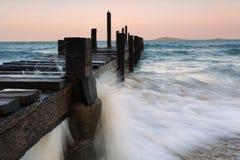 Rocks på stranden och träpir Fotografering för Bildbyråer