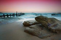 Rocks på stranden och träpir Arkivbild