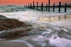 Rocks på stranden och träpir Arkivfoton