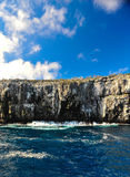 Rocks in the Pacific Ocean cut water from the nice blue sky. Royalty Free Stock Image