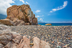 Rocks and pebble beach at Bussaglia on west coast of Corsica Stock Photos