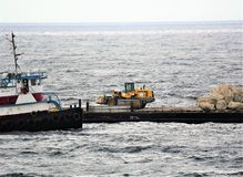 The first pile of rocks is almost all in the ocean for the new reef just offshore. The rocks are picked up and dropped overboard in order to help develop areas royalty free stock image