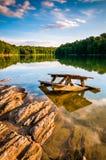 Rocks and a picnic table in Lake Marburg, at Codorus State Park, Royalty Free Stock Image