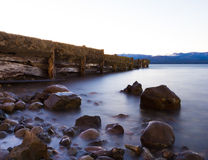 Rocks and pier in the lake Stock Image