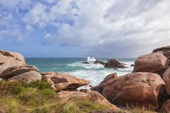 Rocks at Ploumanach, Pink Granite Coast, France. Huge boulder and the boiling sea at Ploumanach, Pink Granite Coast in Brittany Stock Photography
