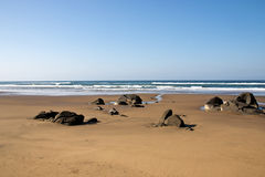 Rocks Protruding from Sandy Beach at Low Tide Stock Photography