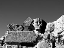 Rocks, Pyramid & Cheops. In the foreground, the remains of an ancient stone monument, then head of the Sphinx and the tip of the Great Pyramid of Giza, Cairo Royalty Free Stock Photo