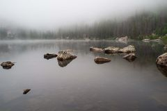 Rocks reflected in a foggy lake Stock Photo