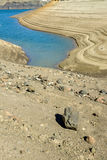 Rocks rest on terraces on lowering wafer in a reservoir Royalty Free Stock Photos