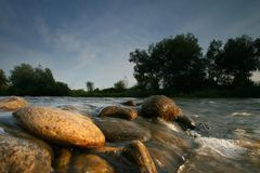Rocks in the river bed. River stones in sunset light Stock Photo