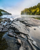 Rocks in a river at sunrise in the mist. The mist rises and sun hits the trees as the river reflects the sky in the pools between the rocks Stock Photo
