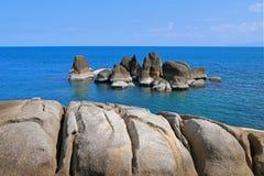 Rocks at rocky seashore against blue sea water and sky at Koh Sa Royalty Free Stock Photo