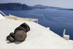 Rocks on roof in Oia Santorini. A close up of rocks on a roof and the sea coast in the background, Oia, Santorini, Greece stock photo