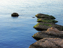 Rocks in a row in the sea Stock Image