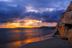Rocks and sand in Alghero shore at sunset Royalty Free Stock Photography