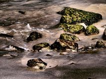 Rocks On The Sand. Beach side scene of rocks washed by water Royalty Free Stock Photography