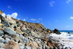 Beach with Rocks and Sand and Blue Sky Royalty Free Stock Images