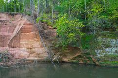 Rocks of sandstone overgrown with plants and moss, river flow. stock images