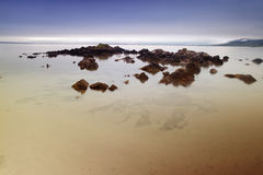 Rocks on sandy beach in smooth calm sea Stock Photography
