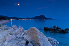 Rocks and sandy beach under the moon shine after twilight Stock Images