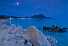 Rocks and sandy beach under the moon shine after twilight Royalty Free Stock Photos