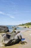 Rocks Scattered on Beach. Landscape shot looking down a beach Royalty Free Stock Photography