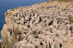 Rocks by the sea. Strangely eroded carbonate sedimentary rocks forming a cliff to the ocean. Nau dos Corvos, Peniche, Portugal Stock Photography