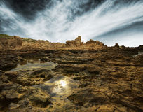 Rocks beside the sea against a dramatic sky in sep Stock Photography