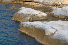 Rocks in the sea bathed in afternoon light in Akanthou, near Kyr Stock Image