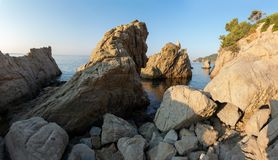 Rocks on sea coast in Lloret de Mar, Spain. Cliff on rocky beach in Costa Brava. Picturesque seaside. Landscape with stones on mediterranean bay on clear royalty free stock images