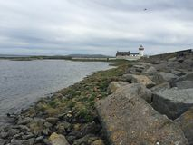 Rocks sea and lighthouse in Galway, Ireland Royalty Free Stock Photo