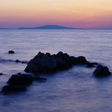 Rocks in the Sea and Island after Sunset Stock Images