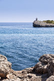Rocks, sea and lighthouse Stock Photos