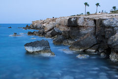 Rocks at the sea, long exposure. Rocks at the blurred sea water, long exposure Stock Photography