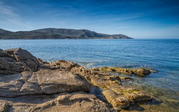 Rocks and sea overlooking La Revellata lighthouse in Corsica Stock Photo