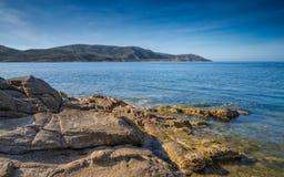 Rocks and sea overlooking La Revellata lighthouse in Corsica Stock Photo